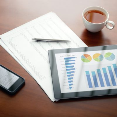 Modern workplace with digital tablet and mobile phone, pen and papers with numbers.